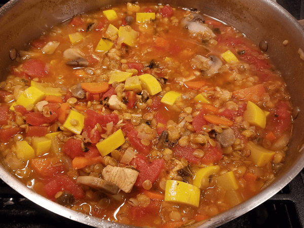olive oil, boneless skinless chicken breasts, onions, yellow squash, summer squash, carrots, mushrooms, dried lentils, basil, reduced-sodium chicken broth, salt, black pepper, Italian tomatoes, pear tomatoes, Roma tomatoes, plum tomatoes, Parmesan cheese